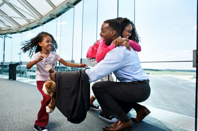 Daughters (7-9, 10-12) greeting father in airport