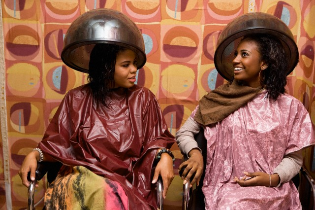 Two women under hair dryer smiling