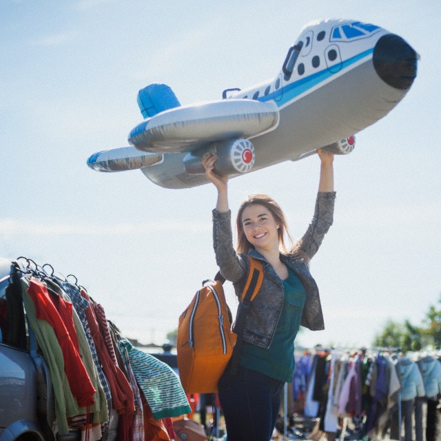 Young woman on flea market with blow up airplane